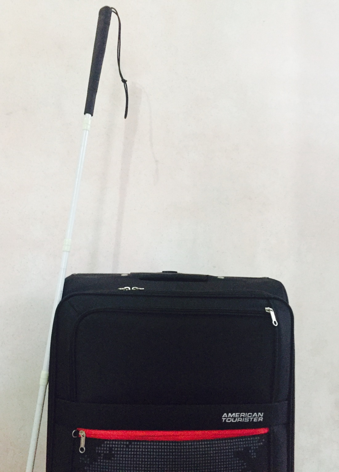 This image contains: White Cane and Black Luggage
